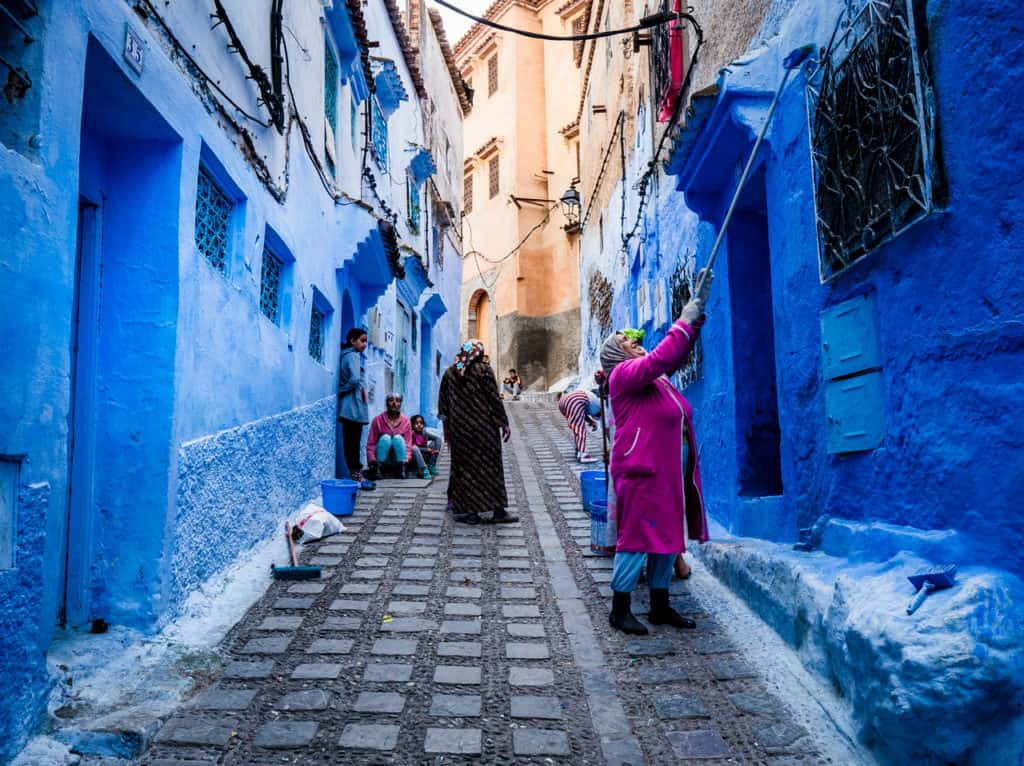 Things to do in and around Chefchaouen, the Blue City of Morocco - streets of Chefchaouen -Why are the streets blue in Chefchaouen - applying new blue paint - Journal of Nomads