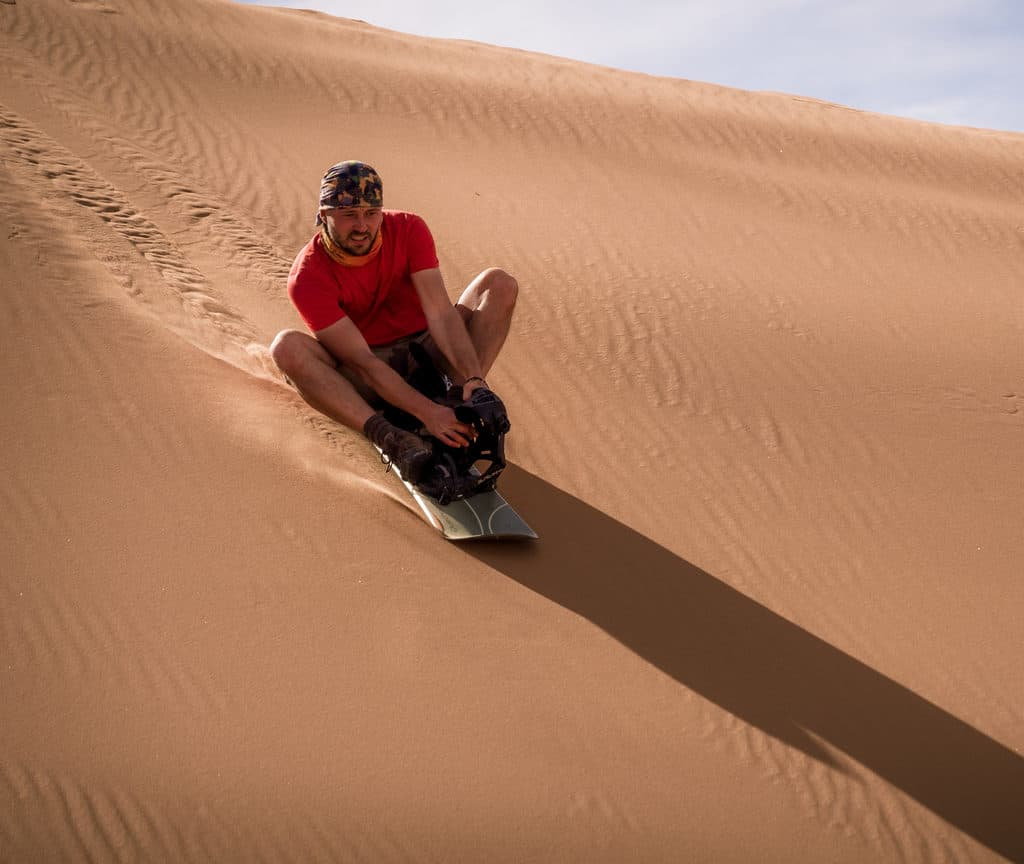 How to plan a desert trip to Merzouga and other fun things to do in the Sahara, Morocco. - Journal of Nomads - sandboarding in desert