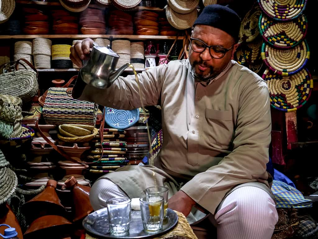 Photography tips for Morocco - Man pourring tea in Essaouira - Journal of Nomads